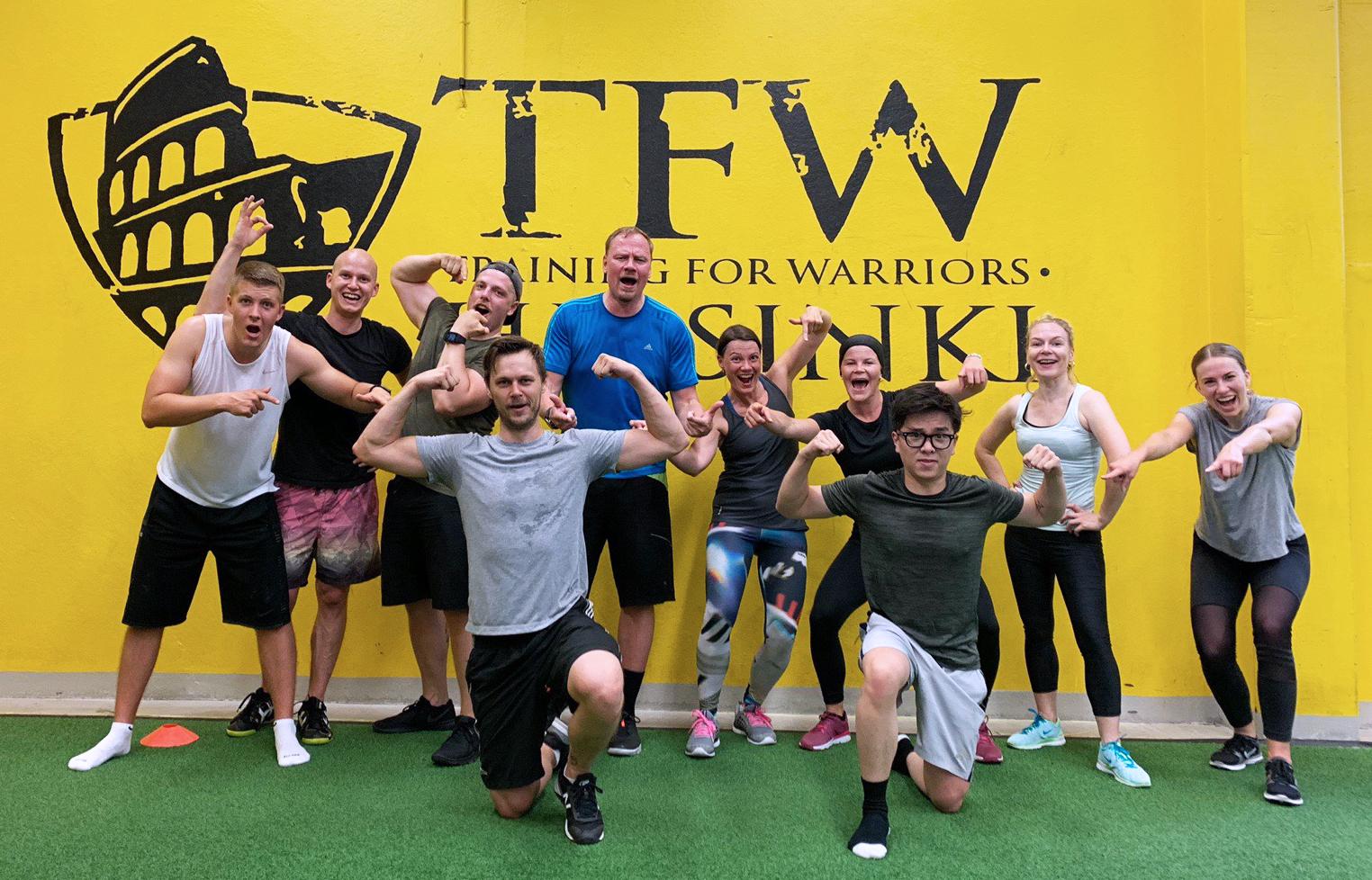 Ryhmäkuva kymmenestä allerilaisesta Training for Warriors-salin kuvausseinän edessä treenin jälkeen