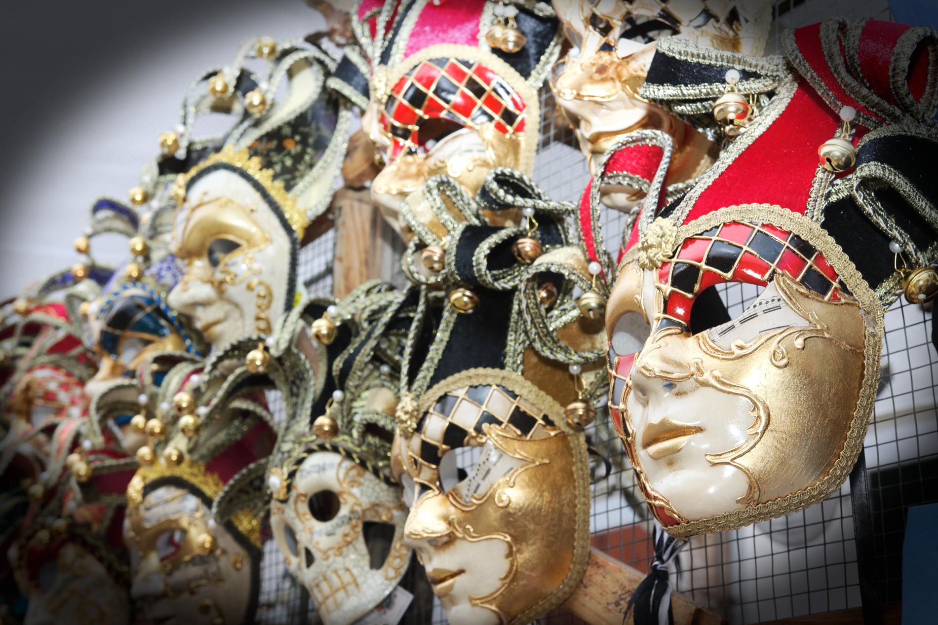 Joukko erilaisia, koristeellisia naamioita seinällä