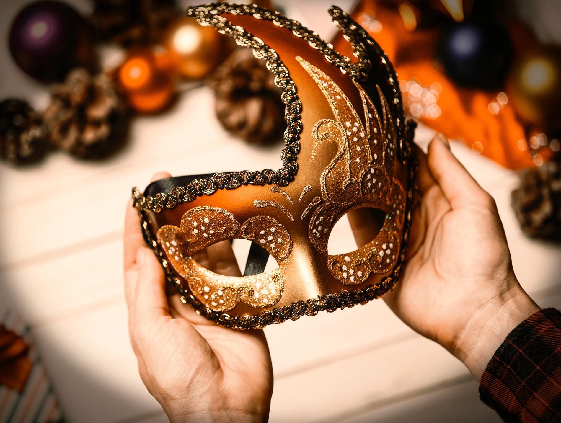 Kädet pitelevät koristeellista naamiota