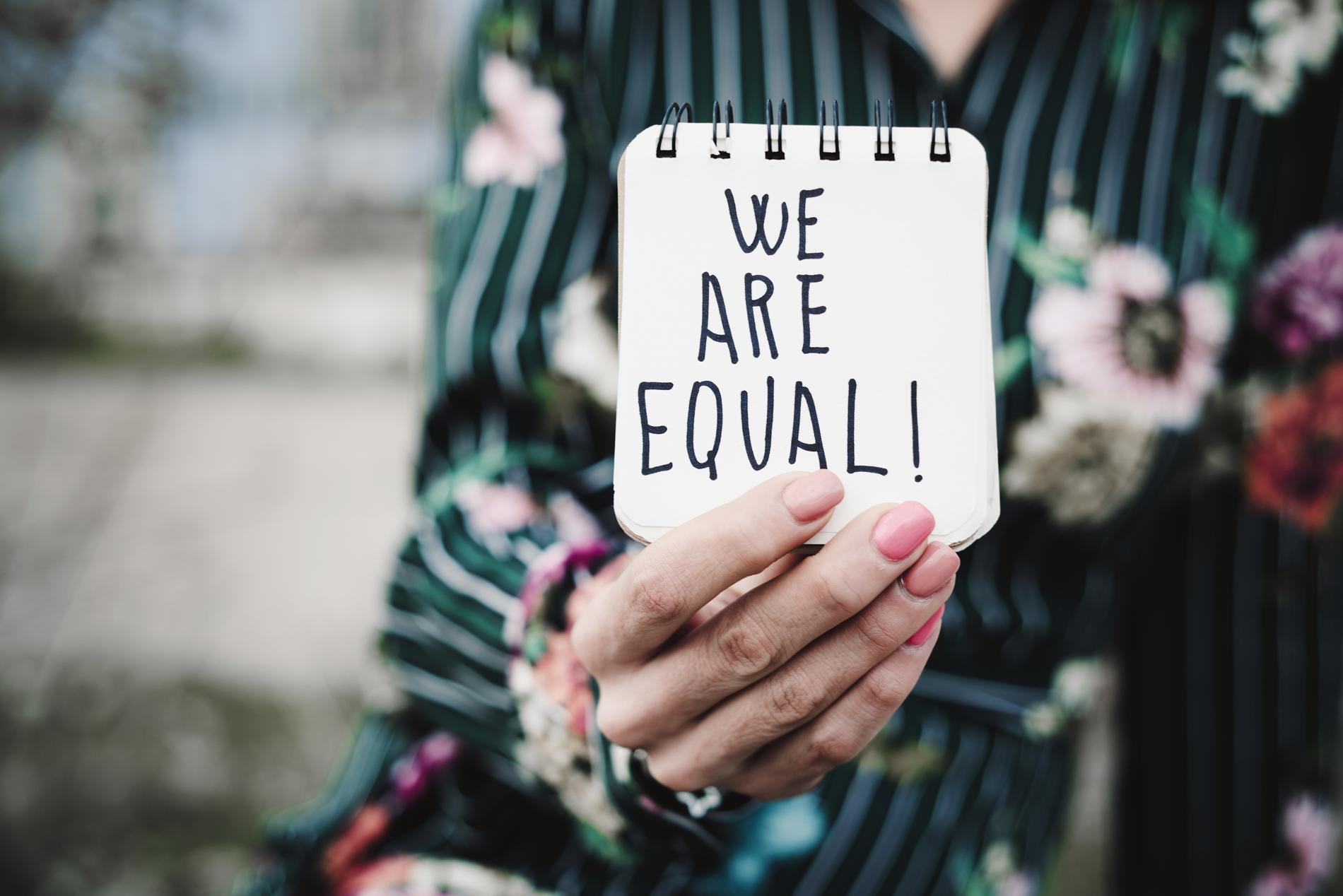 """Naisoletetun käsi pitelee vihkoa, johon on tussilla kirjoitettu: """"We are equal!"""""""