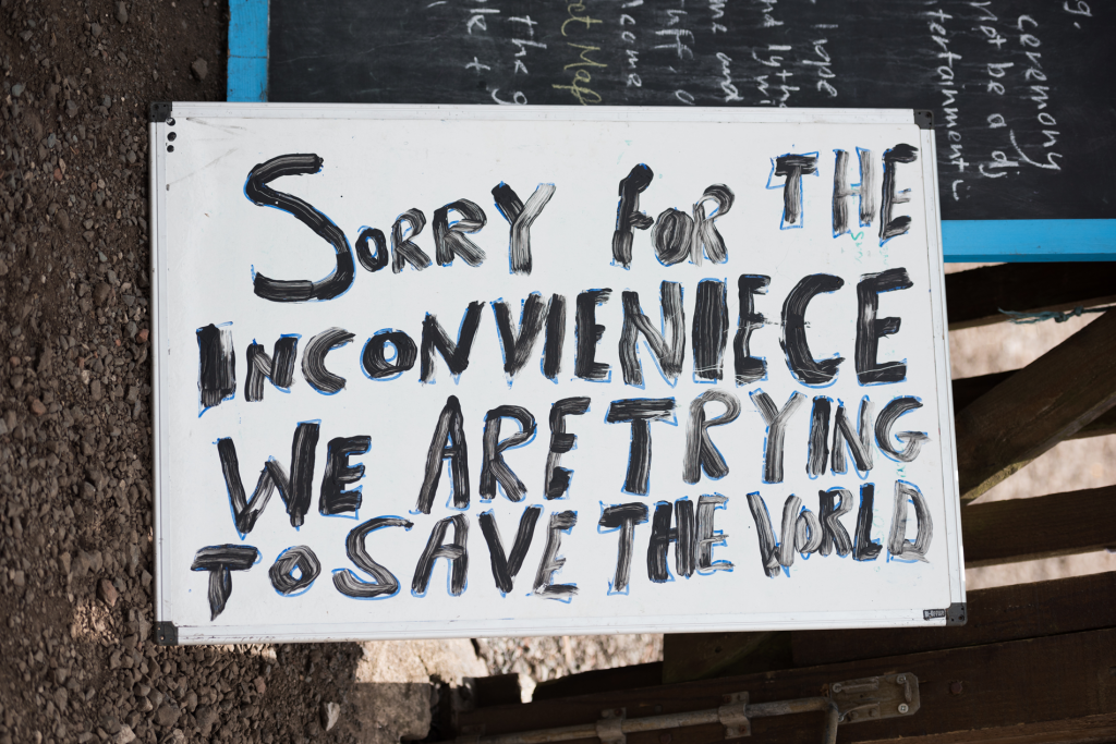 """Kyltti, johon on maalattu teksti: """"Sorry for the inconvenience, we are trying to save the World"""""""