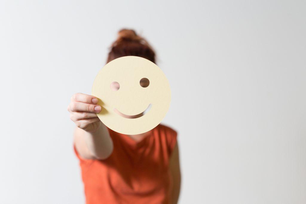 Ihmishahmo ojentaa paperista leikattua hymynaamaa kameraa kohti niin, että se peittää oikeat kasvot