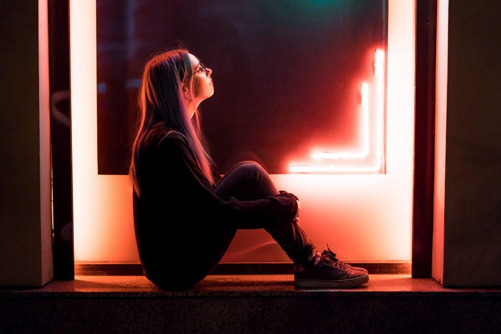 Nuori naisoletettu istuu neonvaloilla valaistun laatikon keskellä