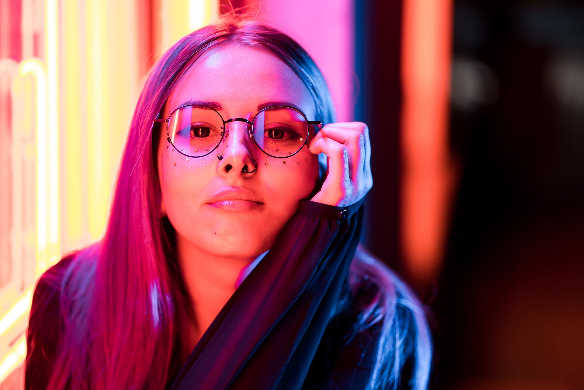 Nuori naisoletettu korjaa silmälasiensa asentoa ja katsoo kiinnostuneena tarkemmin kohti