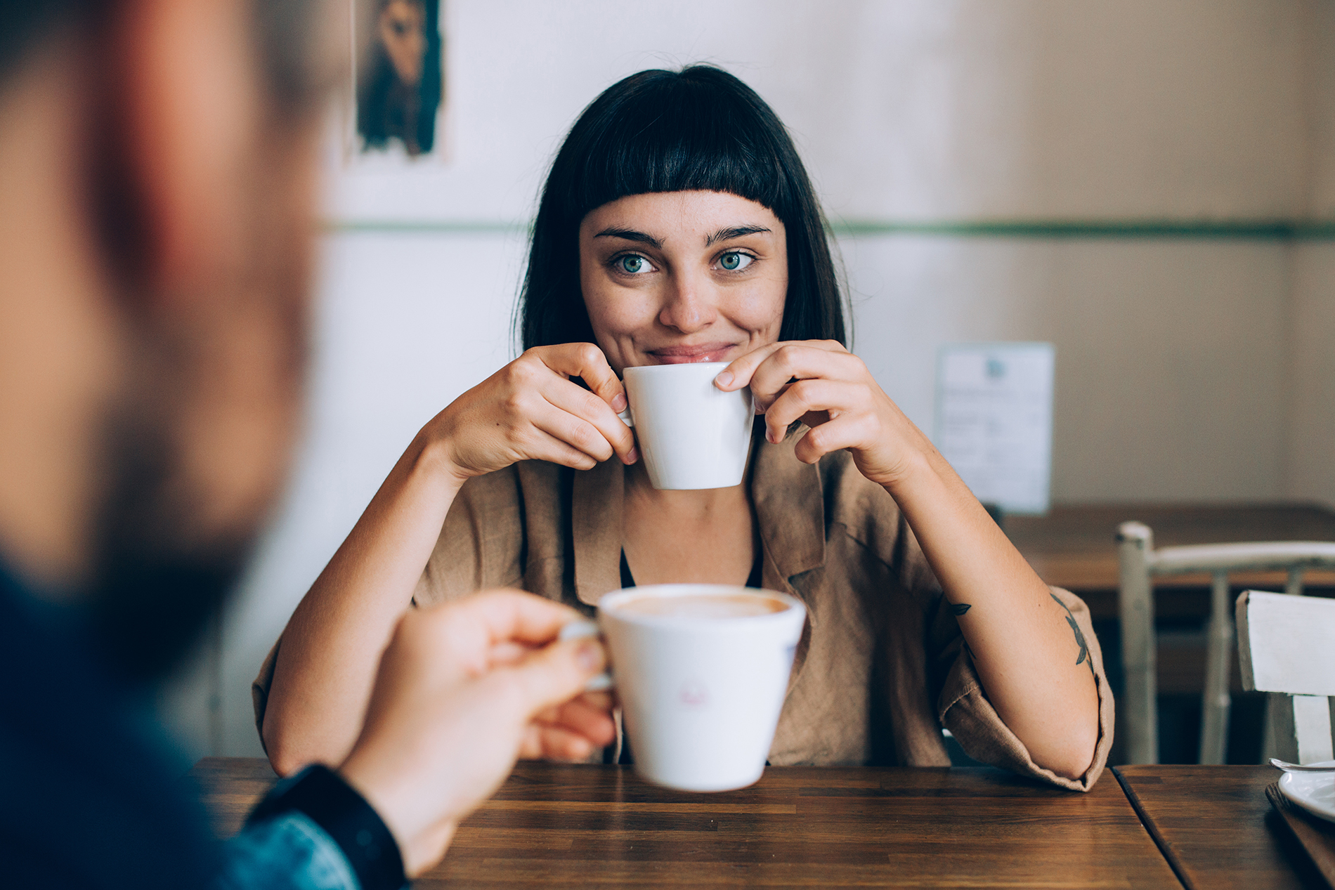 Nainen katsoo hurmaavasti kahvikuppinsa takaa kahvilassa